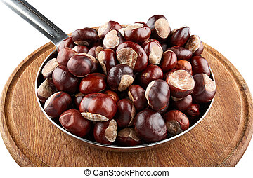 Many chestnuts in frying pan on wooden plate
