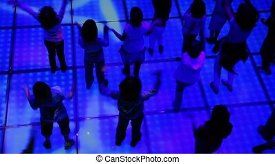 Many children dance at discotheque, closeup view from above