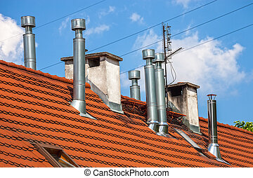Many chimneys - Chimneys on a building rooftop against a...