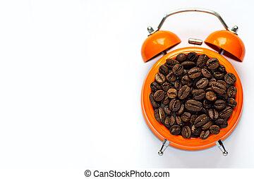 many coffee beans in orange alarm clock on white background