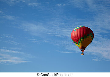 Many-colored hot air balloon with people fly in the blue...