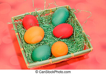 Many colored painted easter eggs in a basket with green grass, close up background.