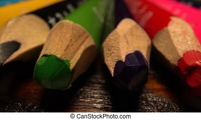 Many colored pencils lie in row. Sliding over pencils on table. Macro shot on laowa lens