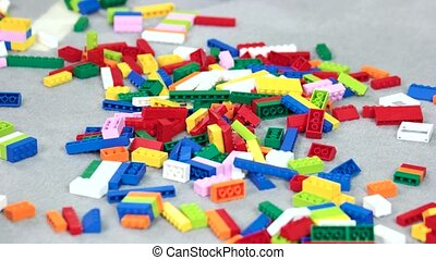 Many colorful constructor blocks on floor in the room. Close...