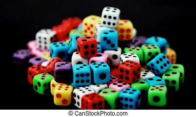 many colorful dice stacked in hill rotate on black