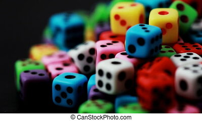 many colorful dice stacked in pile rotate on black