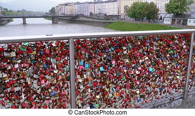 Many Colorful Locks Hanging on Handrails on Love Bridge in Salzburg, Austria. Makartsteg Bridge covered in love locks with pedestrians walking over the Salzach River, City Centre. Rainy Weather
