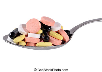 Many colorful pills in spoon