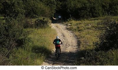 many cyclists riding on a mountain road on a mountain bike.