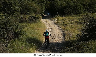 many cyclists riding on a mountain road on a mountain bike.