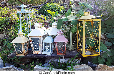 Many decorative colorful candle lanterns on the garden