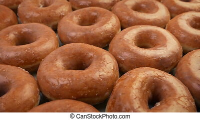 Many Delicious Hot Donuts - Moving slowly over tasty glazed...
