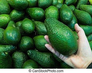 Many delicious ripe avokado background. Avokado in hand - ...