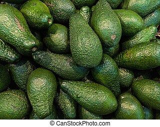 Many delicious ripe avokado background. Avokado on market - ...