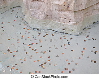 Many different coins under water in a fountain
