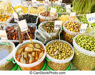 Many different olives, dried fruits on the market close-up