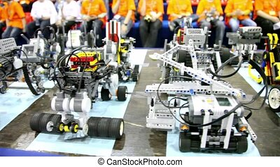 Many different oy robots stand on table at background of...