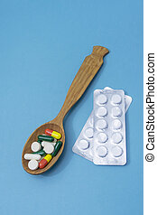 Many different pills and capsules of medicines in wooden spoon on blue background. Copy space, selective focus. The concept of medication, medicine, pharmaceuticals