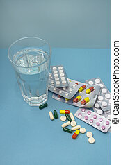 Many different pills of drugs are scattered and in blisters on a blue background. A glass of clean water for medication. The concept of treatment, against a virus, health