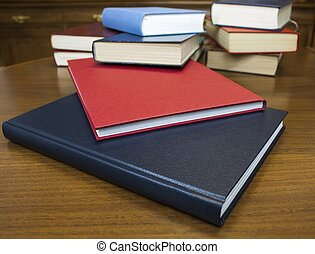 Many different sized colored and shaped books on wood table