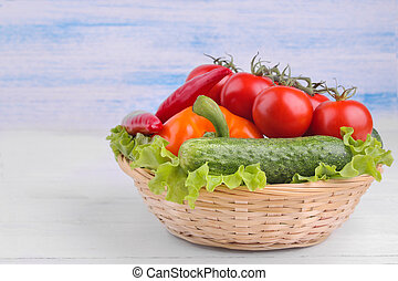 Many different vegetables in the basket including, tomatoes, pepper, cucumbers and lettuce on a white and blue wooden background.