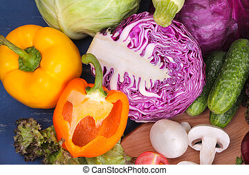 Many different vegetables include cabbage, zucchini, tomatoes, peppers, mushrooms and cucumbers on a blue wooden background. top view