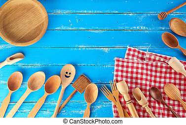many different wooden spoons, forks and empty plate on a blue background