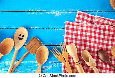many different wooden spoons, forks on a blue background