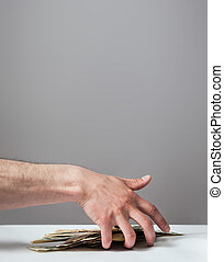 Many dollars falling on man's hand with money