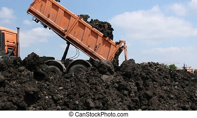 Many dump trucks are unloading soil at the same pile. -...