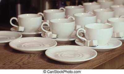 many empty white clean tea cups - male barman prepares clean...