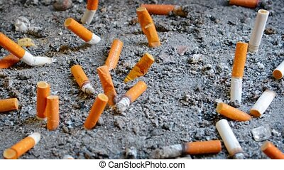 Video Full HD - Dozens of extinguished cigarette butts of varying brands, discarded in a designated receptacle, many protruding from the sand.