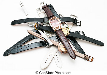 Many female`s wristwatches with leather wristlets on white ...