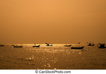 many fishing boat on the sea at sunset. silhouette