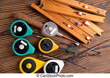 Many fishing rods for winter fishing on a brown natural wooden background