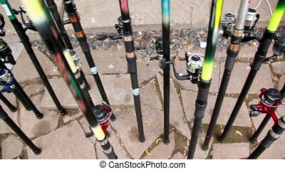 Many fishing rods stand on pavement near wall, closeup view...