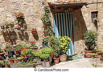 many flowerpots in front of tuscan house - with entrance ...