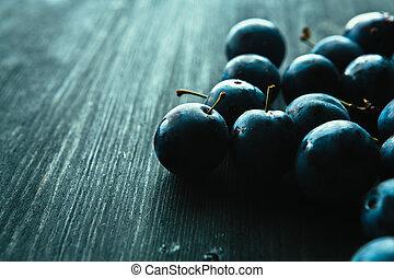 many fresh plums on black background close up