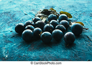 many fresh plums on blue background close up
