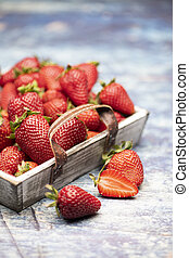 Many fresh, red strawberries in a wooden basket