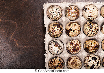 many fresh speckled quail eggs in cardboard container