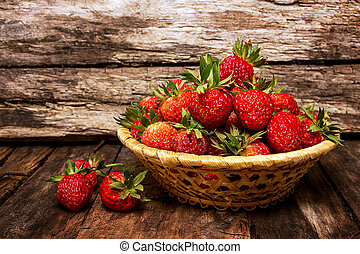 Many fresh strawberries on a wooden background. Useful treat