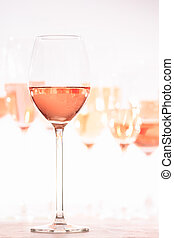 Many glasses of rose wine at wine tasting. Concept of rose wine and variety