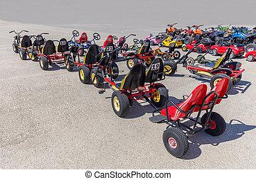 Many go-karts parked on asphalt terrain
