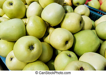 Many green apples in a box closeup