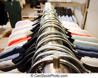 Many hangers on a clothes rack in a fashion store