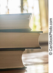 Many Hardcover Old books on grunge wooden table desk shelf in library against color background. Hardback no labels. Education reading concept. Back to school ideas with copy space room for text.