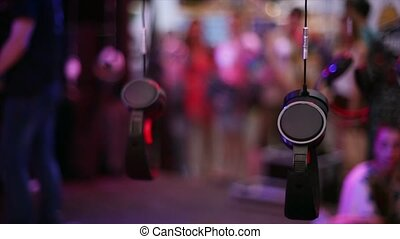 Many headphones hang on wire at open air festival party. Entertainment. Evening. Holidays.