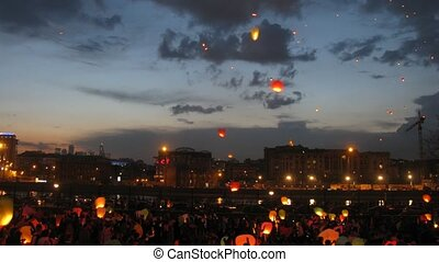 Many heavenly lanterns fly to night sky against floating clouds