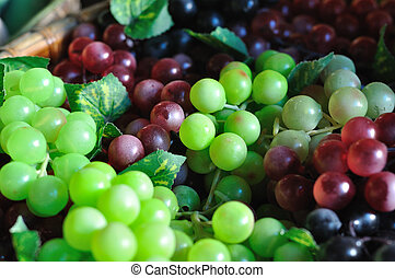 Many huddle color grapes fruit, green, red and black.